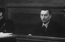 A middle-aged man sitting in the dock of a courtroom