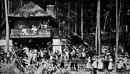 A theatre production, showing a crowd of villagers celebrating outside an inn