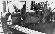 La torre de mando de un submarino mientras está atracado.  Cuatro hombres están parados alrededor de la torre de mando y junto a ella se ha colocado un tablón de pasarela.  También se puede ver la escotilla abierta del submarino y varias cuerdas que amarran el barco.
