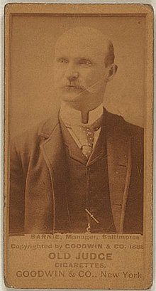 "Baseball card showing a bald, white man with a mustache in a medium shot.  The man is wearing a suit and tie.  The first line of the caption beneath the photo says ""BARNIE, Manager, Baltimore"".  Beneath that the caption says ""OLD JUDGE CIGARETTES"" and ""GOODWIN & CO., New York""."