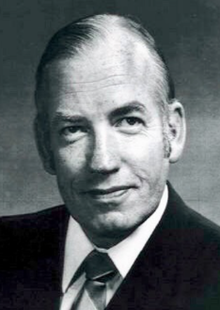 Black and white photo of Calcutt in a suit and tie