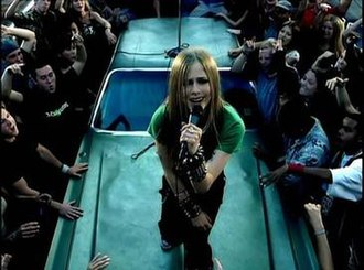 Sk8er Boi - Lavigne, wearing her famous tie, sings on top of a car on the street.