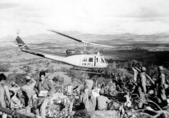 Air America (airline) - Air America Bell 205 helicopter leaving a Hmong fire support base in the Laotian Plain of Jars, c. 1969
