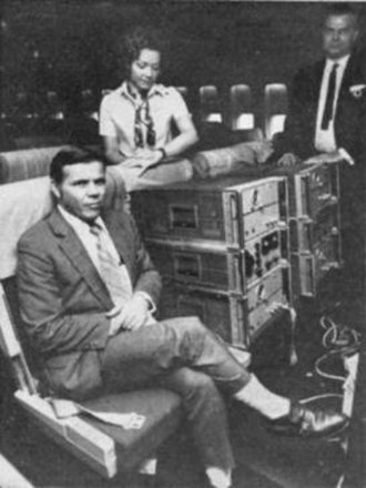 Hafele–Keating experiment - Hafele and Keating aboard a commercial airliner, with two of the atomic clocks and a stewardess ironically checking her wristwatch.
