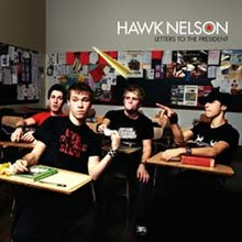 All of the band's members sitting in desks in a classroom setting