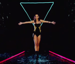 """In Your Eyes (Inna song) - Shot from the music video, showcasing its use of neon and water effects. This and other aspects led its visual being likened to Rihanna's """"Pour It Up"""" (2013)."""