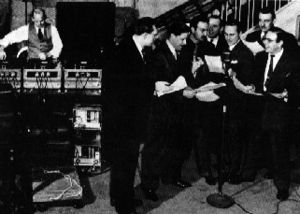 Mutual Broadcasting System - A recording session for The Mysterious Traveler, with the entire cast clustered around one microphone. Host Maurice Tarplin is directly behind the mic, third from the right. To the rear, a sound-effect artist and three phonographs (at least) provide music and effects.