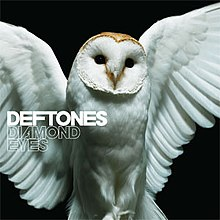 "A barn owl is shown with its wings open in front of a black background. On the complete left side of the border, the words ""Deftones"" and ""Diamond Eyes"" are shown."