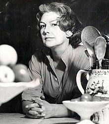 middle aged woman with dark, greying, hair; she is at a kitchen table, looking towards the camera