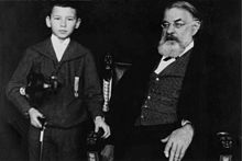 Joachim and the young Franz von Vecsey. Note the strongly incurving, arthritic first finger of his left hand. The chair in which he is sitting was a special present to him. He willed it to Donald Tovey, and it is now owned by the University of Edinburgh Museum.[74] (Source: Wikimedia)