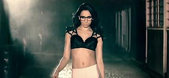 """Bring It (song) - An image of Jodie Connor in the dark alley scene wearing just her bra and tights in the music video for """"Bring It""""."""