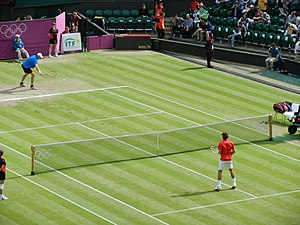 Tennis at the 2012 Summer Olympics - John Isner and Roger Federer warming up prior to their men's singles quarterfinal match on Centre Court