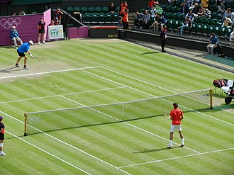 Tennis at the 2012 Summer Olympics – Men's singles - John Isner (United States) and Roger Federer (Switzerland) warming up for their quarter-final match on Centre Court.