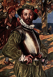 A bearded man, wearing green shirt and doublons, stands with his hands on his hips. The sea is visible in the background. A cuirass (metal armor) protects his upper torso. He is also wearing a green hat with a red rose and a white ruff on his neck. A rapier hangs ready at his left hip. Behind him on his right, a man is walking by, carrying a laden rucksack over his shoulder.