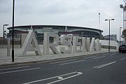 View of the South Bridge with the ARSENAL statue lettering in the foreground and the Emirates Stadium in the background.