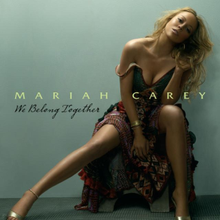 "A blonde woman sitting in a chair in front of a light blue background, and wearing a patterned dress. ""Mariah Carey"" is written on her image in green font, with ""We Belong Together"" written in black, cursive font below it."