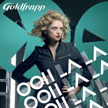 "CD cover with a blond-haired woman at the centre standing with her hands on her hips and looking off to the right of the image. Text overlays the woman and the bottom right of the image saying ""Ooh La La"" three times. Text in the upper left corner says ""Goldfrapp"" along with a small text box stating ""Ooh La La Including Exclusive New BSide"". In the background is a black wall along with two teal-colored circles with triangle-shaped holes cut out of them."