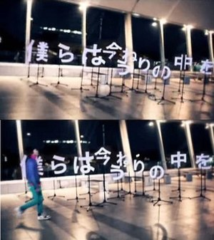 "Aruku Around - The typographic objects used in the video for ""Aruku Around"" were praised by critics from the Japan Media Arts Festival. The shot above shows the objects from a misaligned angle, while the shot below shows vocalist Ichiro Yamaguchi walking past the objects as they become properly aligned in time to the song's lyrics."