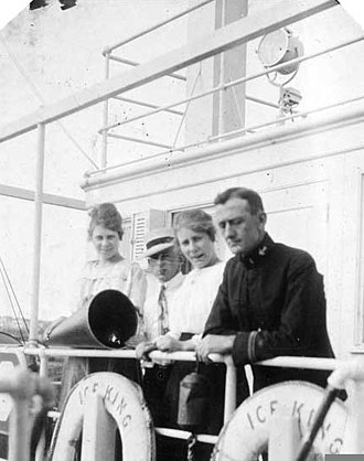 USS Ice King (ID-3160) - Passengers and a junior naval officer standing at a railing at the rear of the ship's pilot house circa August–September 1919.