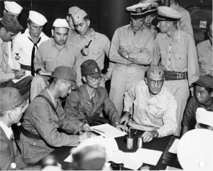 Lawson H. M. Sanderson - General Sanderson (seated in the center) accepts Japanese surrender of Wake Island from admiral Shigematsu Sakaibara (second from the left).