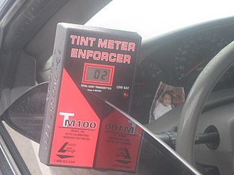 Window film - Photo of vehicle with illegal window tint being measured at 2% light transmittance.