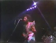 Garry Shider in 1976 touring with Parliament-Funkadelic. He is in his trademark diaper look. The is 23 years old and playing guitar, standing in front of a microphone and preparing to sing.
