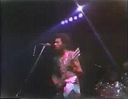 Garry Shider in 1978 touring with Parliament-Funkadelic. He is in his trademark diaper look. The is 23 years old and playing guitar, standing in front of a microphone and preparing to sing.