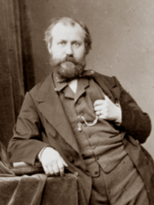 photograph of man in early middle age, balding, with neat moustache and beard