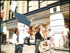 "Gremlins 2: The New Batch - Director Joe Dante (left) holds a cardboard ""Bat Gremlin"", with actor Dick Miller (arms raised). A stop motion model replaced the cardboard gremlin in post-production."