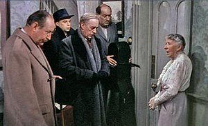 """Mrs. Wilberforce confronts Professor Marcus and his """"ensemble"""""""