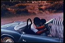 A frame of a man and woman kissing in a convertible sports car; the clapperboard is visible in the edge of the frame