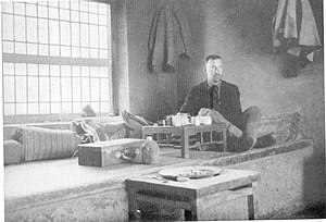Kang bed-stove - A European sitting on the Kang in his room in a Chinese inn