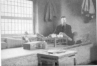 Kang bed-stove - A man, possibly Harry A. Franck, sitting on the Kang in his room in a Chinese inn