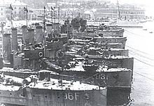 a black and white photograph of several ships at a dock