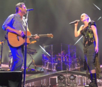 A color picture of singer Gwen Stefani and Blake Shelton performing the aforementioned song live.