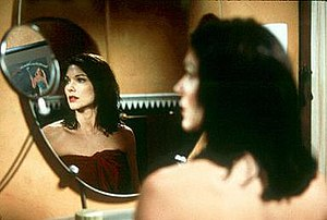 Laura Elena Harring wet from a shower and wrapped in a red towel, looking into the mirror at a reflection of the theatrical poster for the film Gilda