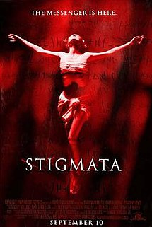 A washed out red image of a woman with arms oustretched as if being crucified