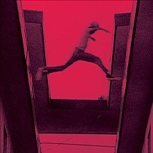 A red-tinted film still showing a boy jumping from one roof to another