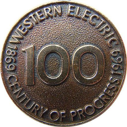 1969 Western Electric keychain medallion celebrating the 100th anniversary of the company's founding, made from the company's recycled bronze metal of scrapped telephone equipment and issued to employees with an inscribed personal registration number. Western Electric 1969 medallion - century of progress.jpg