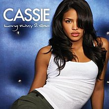 A portrait in the background colour of varied blue featuring the front profile of a young woman posing. The woman's black hair is covering the left side of her face. She is wearing visibly red lipstick and a white, sleeveless top. To her right, in white capital letter font is her name 'Cassie' and below it in a reduced size of the same font is the title 'Long Way 2 Go'.