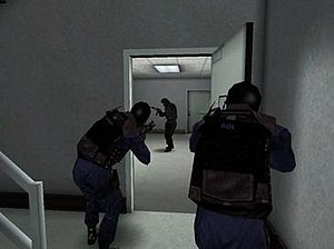 SWAT 3: Close Quarters Battle - Computer-controlled SWAT officers confronting an armed suspect whilst clearing a room; the suspect has been stunned by a flashbang thrown through the door immediately prior to entry by the officers.