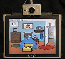 A screen showing a stylised version of a bedroom, mounted on top of the screen is the sensor for a head mouse