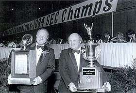 Two men holding trophies