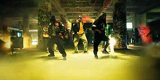 Look at Me Now (Chris Brown song) - The image shows Brown with several dancers, performing intricate routines, which were praised by critics. Additionally, red lights are visible, which were also praised due to the contrast the colorful lasers added to the video.