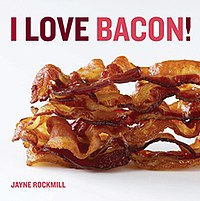 Book cover, white with title at top in bold upper case letters in shades of brown and red. Beneath it a color photograph of a pile of grilled bacon