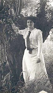 young woman in full-length frock and top coat leaning on a tree