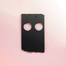 A piece of black plastic on a light pink background
