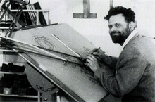 A bearded man in his mid-30s, dressed in a shirt and woolen pullover, is sitting at a drawing board. His pencil is poised in his right hand, and he is smiling off to the left of the camera.