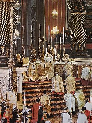 Pontifical High Mass - Papal Solemn Mass celebrated by Pope John XXIII in St. Peter's Basilica in the early 1960s.  Note the presence of multiple assistant priests and ministers, and the mitre and the papal tiaras placed on the altar