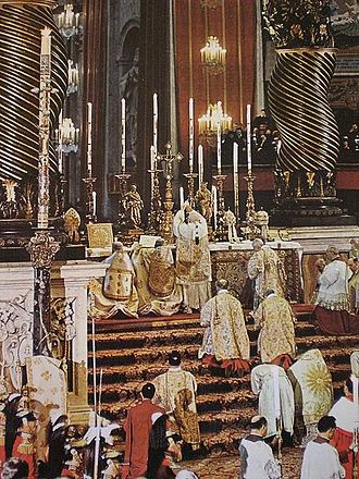 Papal Mass - The Elevation during the papal form of solemn pontifical high Mass celebrated by Pope John XXIII in St. Peter's Basilica in the early 1960s. Note the mitre and the papal tiaras placed on the high altar. The Greek clergy are standing - as is customary - while the others kneel.